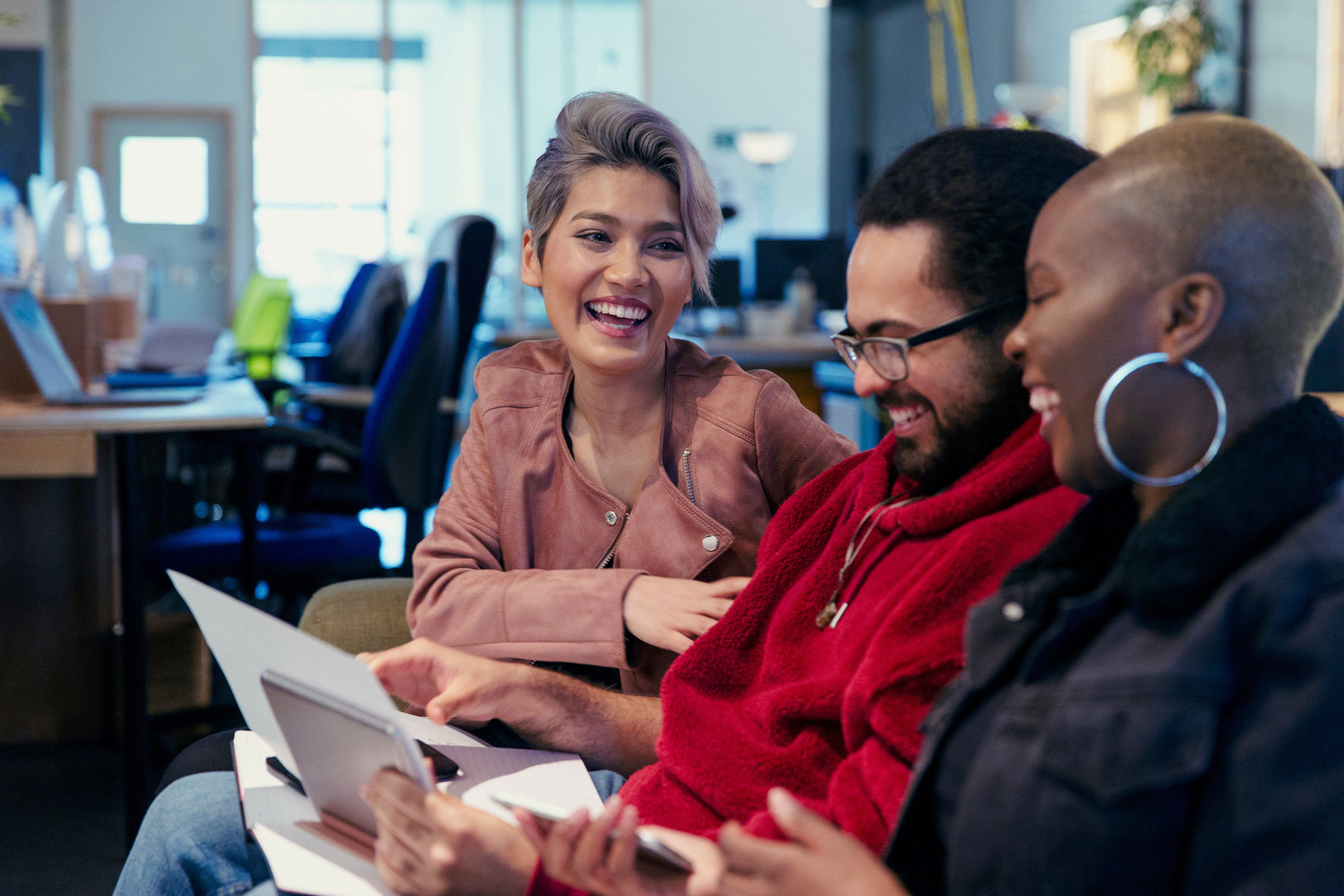 Three business people laughing in office