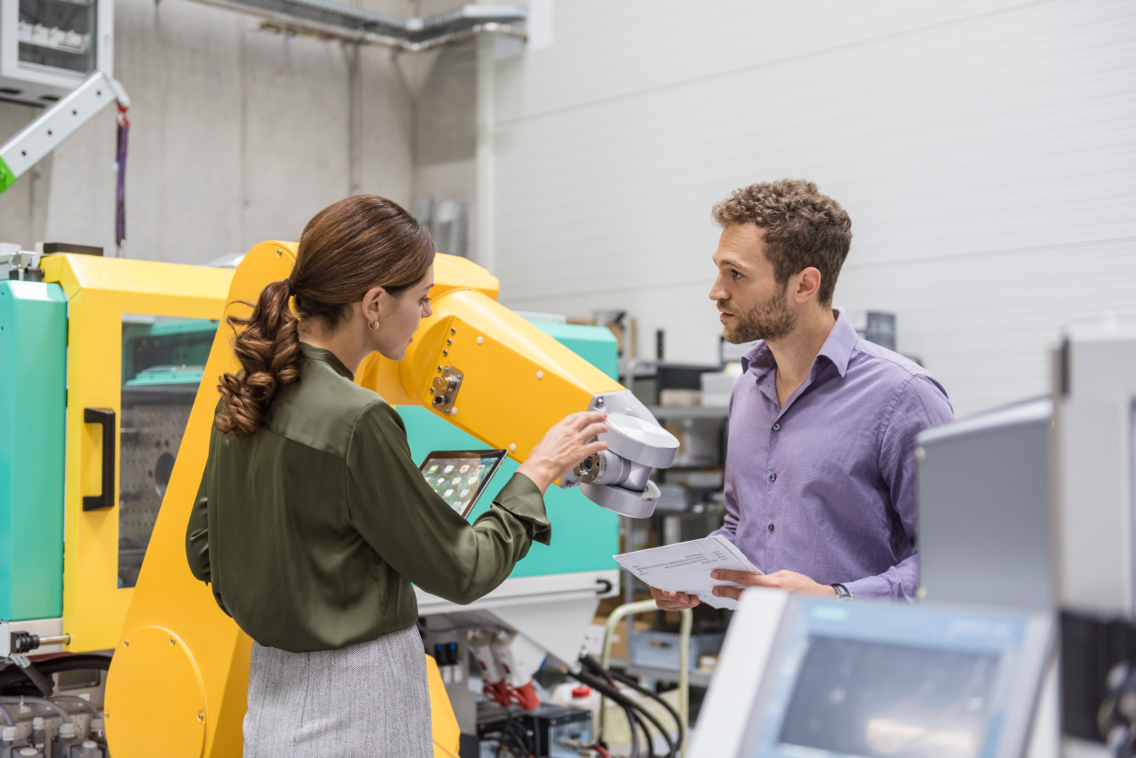Two professionals meeting in front of industrial equipment