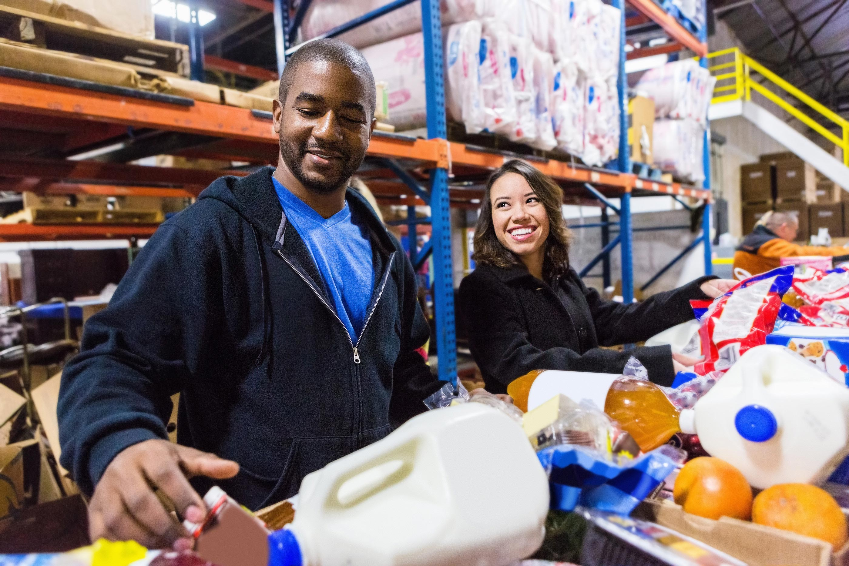 Two volunteers sorting food items