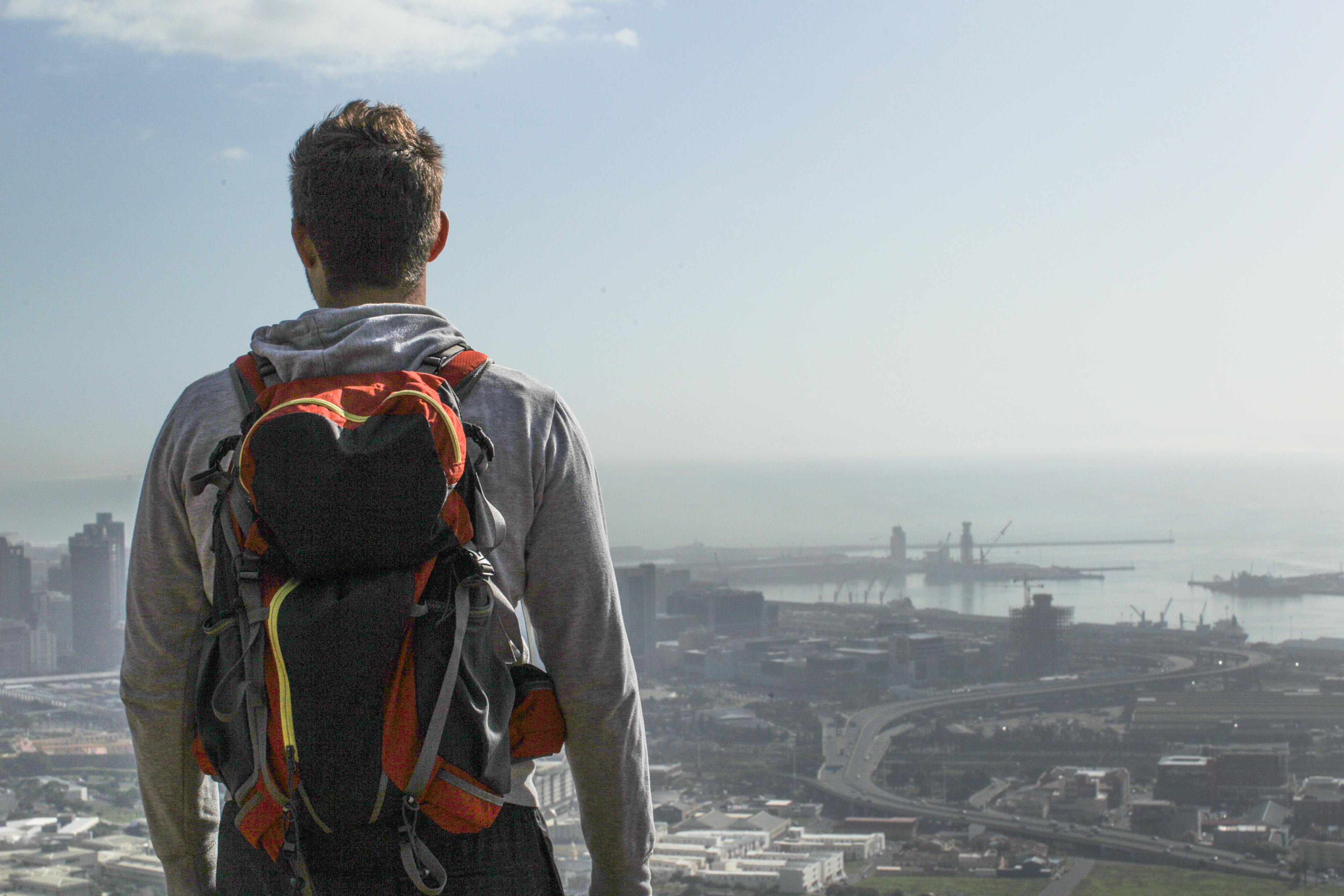 Man with a hiking backpack overlooks a city