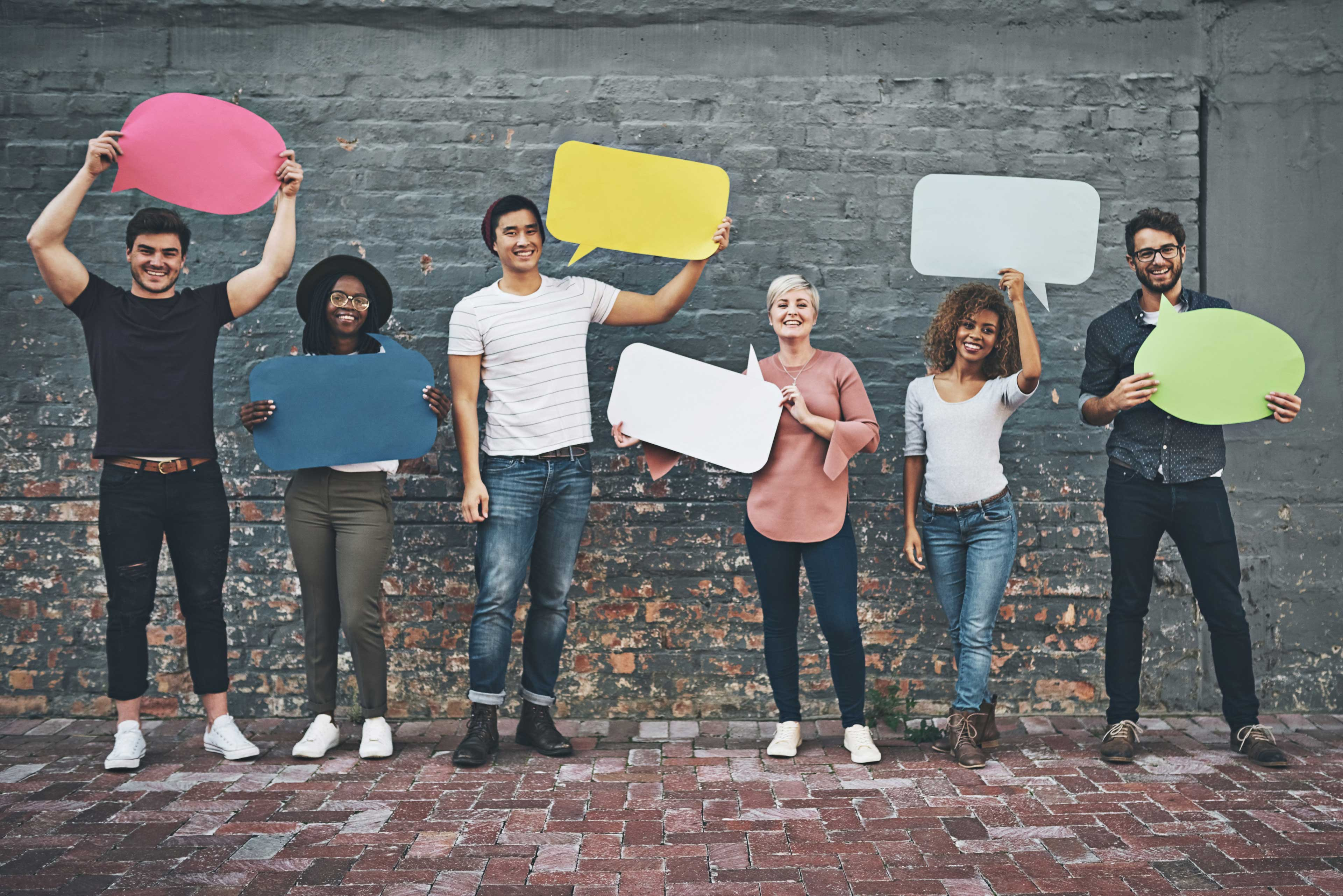 Diverse group of people holding up speech bubbles image