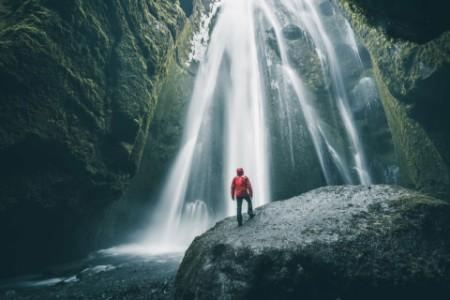 Tourist on a rock admiring a waterfall