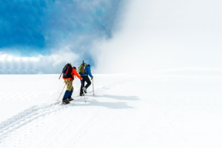 Two hikers climbing snowy mountain