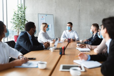 EY - People in face masks sitting during corporate meeting in office
