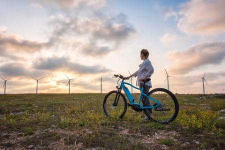 Woman on a bike in wind farm