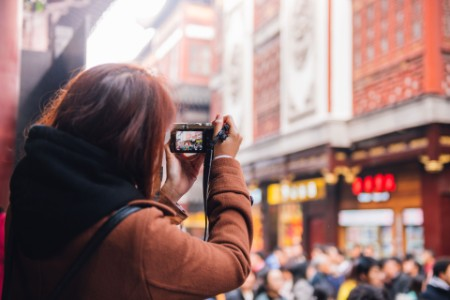 EY - Asian woman taking photo of busy street
