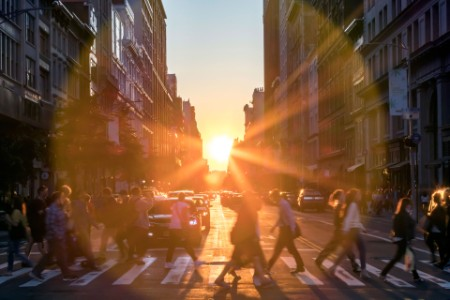 EY - Sunlight rays behind crowds of people in New York City
