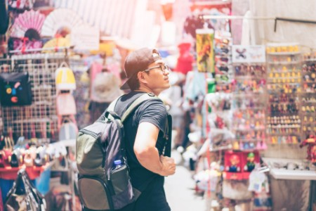 EY - Young man traveler is visiting market