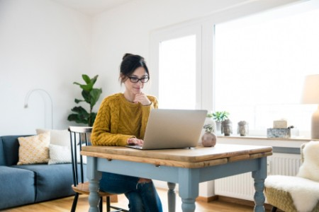EY - Woman-sitting-at-table-using-laptop