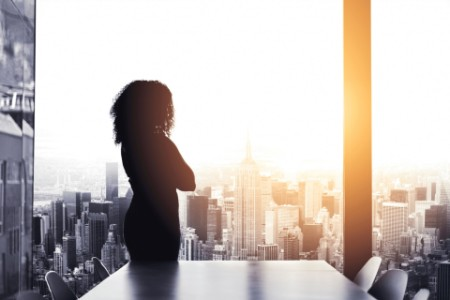 Woman standing in a boardroom looking out the window