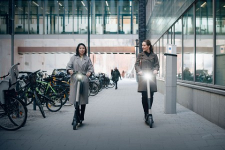 EY - Female colleagues riding electric push scooter on footpath