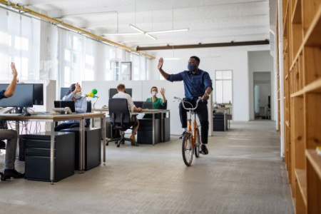 EY - Male professional riding cycle in creative office