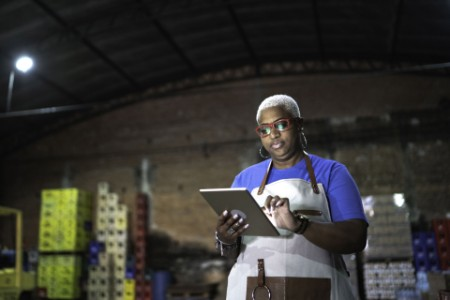 EY - Woman employee using digital tablet at warehouse