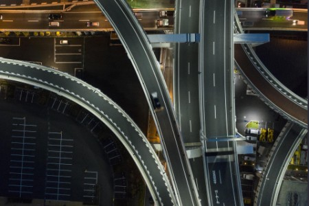 aerial nighttime traffic overlapping road ramps
