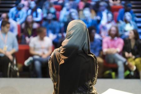 Female speaker in hijab on stage
