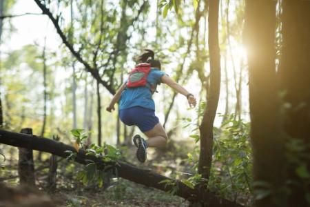 Sportswoman running in tropical autumn forest