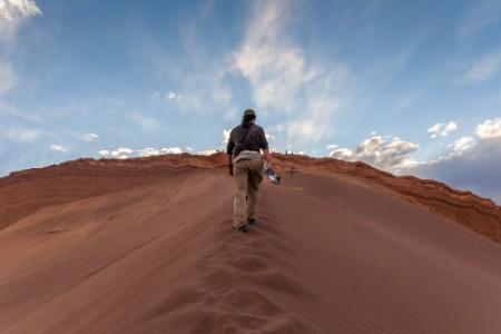 A tourist hiking up a sand dune