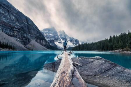 Traveler standing on log in lake