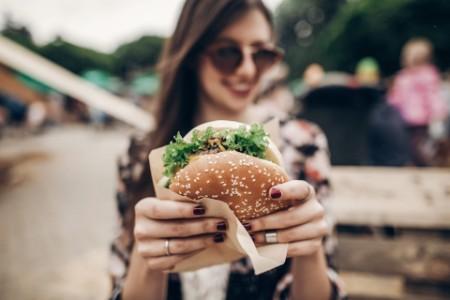 Girl holding hamburger close up