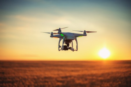 Drone hovering over field