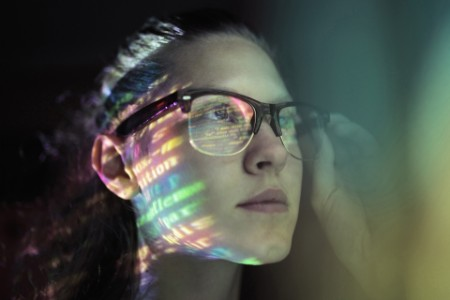 Girl wearing glasses lighted with colorful code