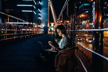 EY - Woman sitting on ground using laptop and mobile