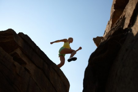 EY - Low angle view of a girl jumping in mountains