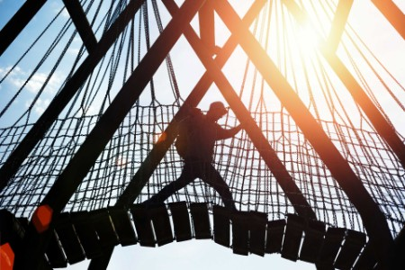 EY - Silhouette of a traveler walking over hanging bridge
