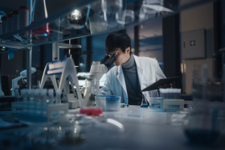 EY - Scientist uses microscope in lab