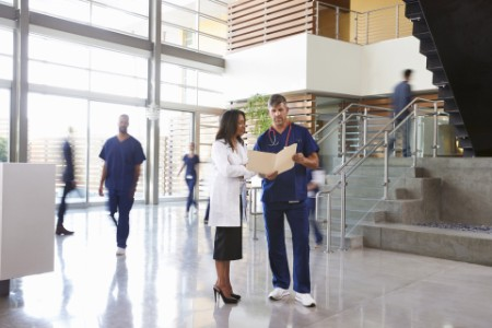 Two healthcare workers talk in the lobby of a hospital