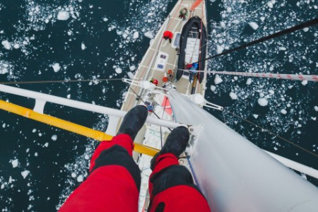ey-sailor-in-cold-weather-gear-standing-on-mast
