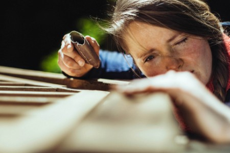 Woman checking her work after grinding an old handrail