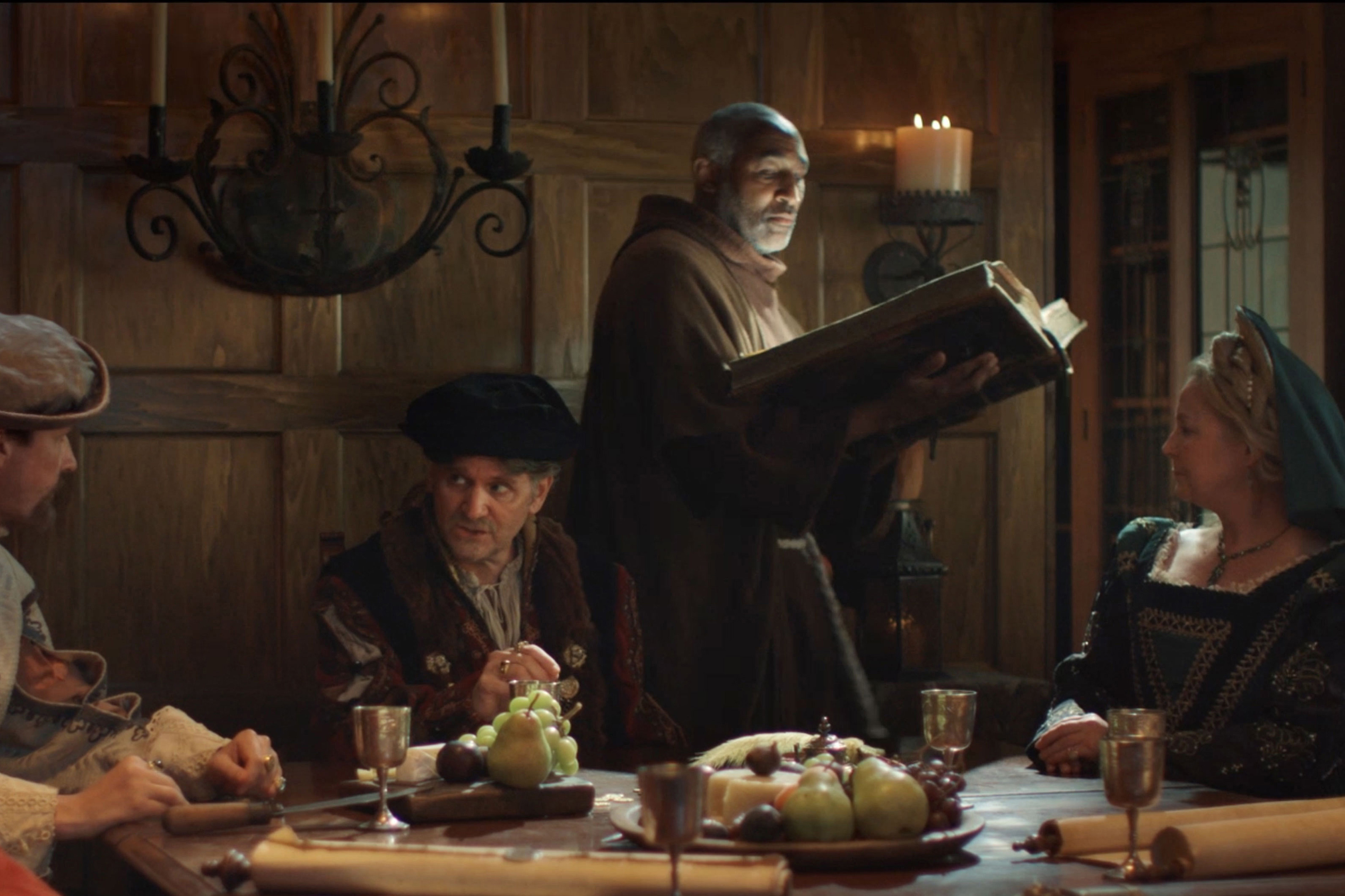 Renaissance era people sitting around a table reading from a book
