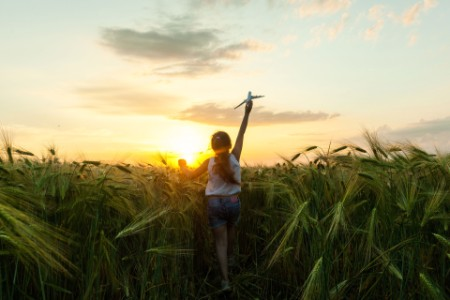 EY - Child girl holding airplane toy during running in the field