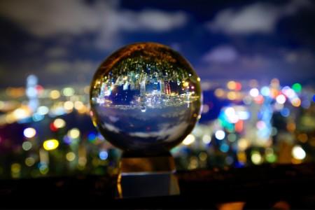 EY - Illuminated city seen in crystal ball at night