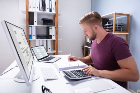 EY - Businessman checking invoice on laptop