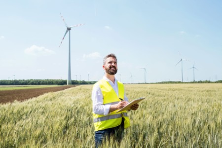 An engineer standing on a field on wind farm