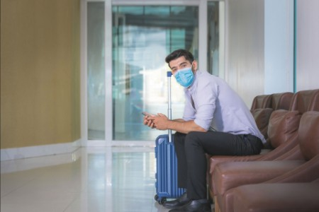 EY - Businessman wearing face mask in lobby of hotel