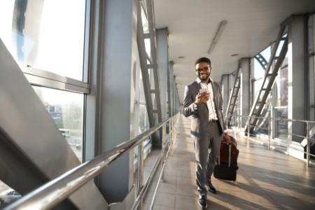 Smiling black entrepreneur walking in airport indoors