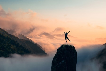 Silhouette of a man jump and rises arms up on a peak