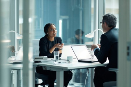 EY - Businesswoman speaking with co-worker in open office