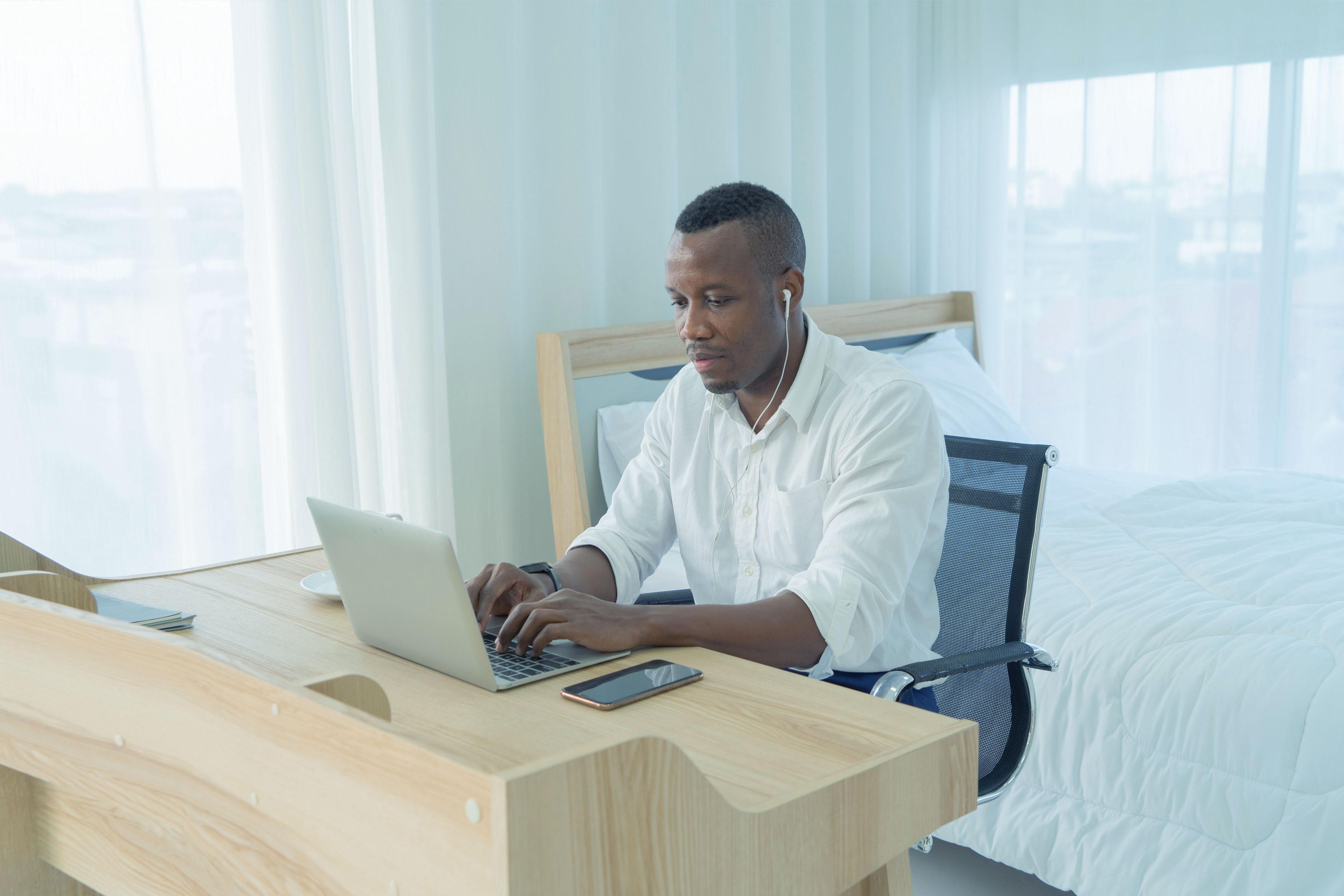 Man working using earphones with computer notebook laptop