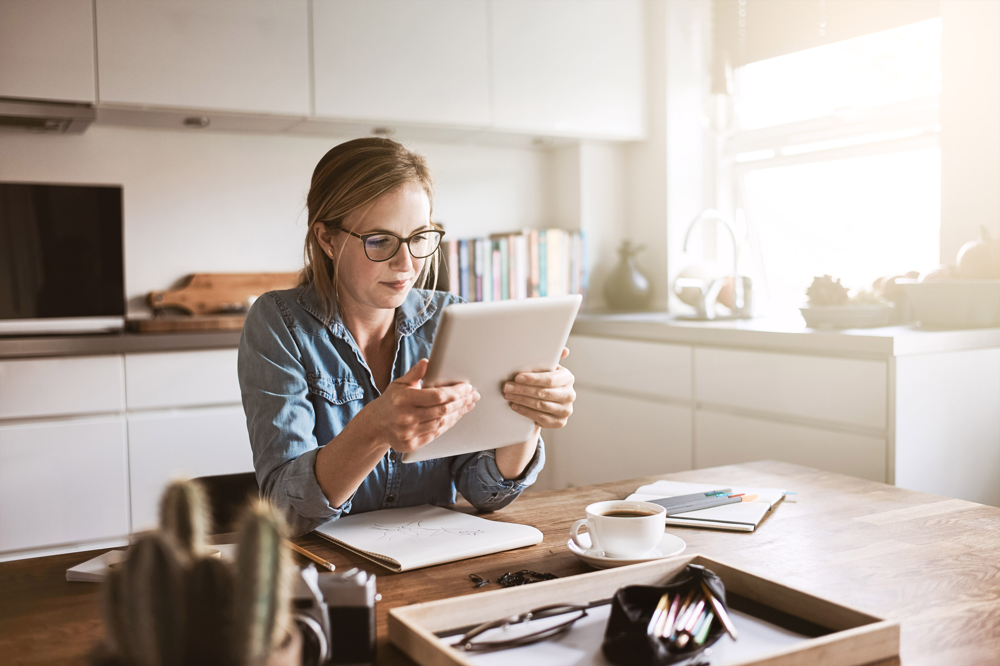 Woman working from home on a digital tablet