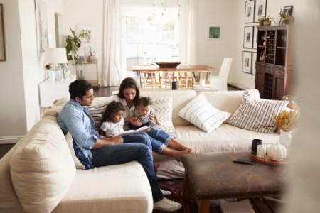 Young Hispanic family sitting on sofa