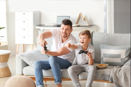 EY - Caucasion man and son playing video games at home