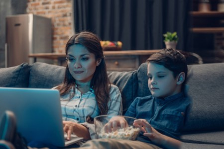EY - Hispanic mother and son streaming movie together
