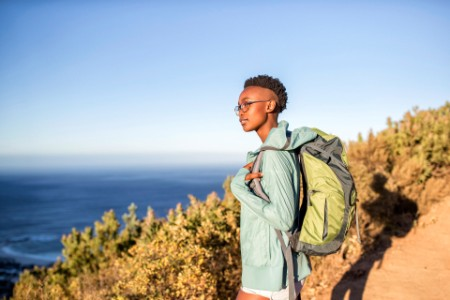 EY - Young woman hiking at the coast looking at view