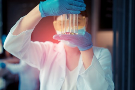 Scientist woman with glasses working reserch and conducts experiments by synthesis compounds in laboratory and the test tube