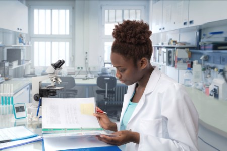 EY - African american female doctor reviewing charts
