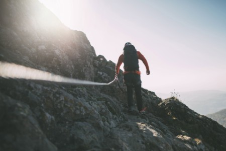 EY - Man with backpack climbing a mountain using rope